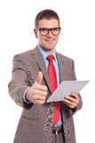 Το νέο επιχειρησιακό άτομο κρατά την ταμπλέτα και παρουσιάζει αντίχειρα Στοκ φωτογραφία με δικαίωμα ελεύθερης χρήσης