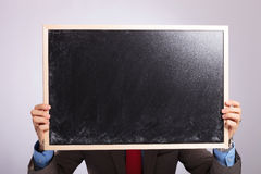 Το νέο επιχειρησιακό άτομο κρατά τον πίνακα μπροστά από το πρόσωπό του Στοκ Εικόνες