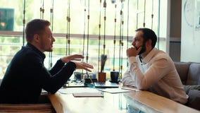 Το νέο επιχειρησιακό άτομο μιλά με τον πελάτη στον πίνακα στο εσωτερικό του καφέ απόθεμα βίντεο