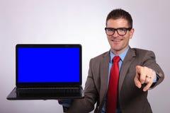 Το νέο επιχειρησιακό άτομο παρουσιάζει ένα lap-top και δείχνει σε σας Στοκ Φωτογραφία