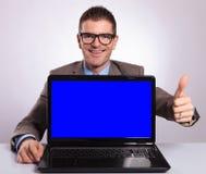 Το νέο επιχειρησιακό άτομο παρουσιάζει το lap-top του με τον αντίχειρα επάνω Στοκ εικόνα με δικαίωμα ελεύθερης χρήσης