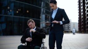 Το νέο επιχειρησιακό άτομο στην αναπηρική καρέκλα επικοινωνεί με το συνάδελφό του για τα έγγραφα textpad απόθεμα βίντεο