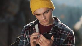 Το νέο ευτυχές άτομο κουβεντιάζει με κάποιο στο τηλέφωνό του που στέκεται στην κορυφή του βράχου πριν από το όμορφο βουνό Επικοιν απόθεμα βίντεο