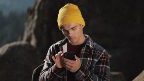 Το νέο ευτυχές άτομο κουβεντιάζει με κάποιο στο τηλέφωνό του που στέκεται στην κορυφή του βράχου πριν από το όμορφο βουνό Επικοιν φιλμ μικρού μήκους
