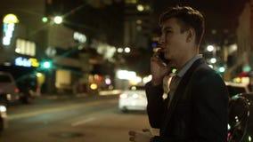 Το νέο ευτυχές άτομο μιλά πέρα από το κινητό τηλέφωνό του σε μια οδό τη νύχτα φιλμ μικρού μήκους
