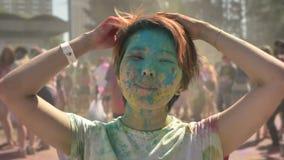 Το νέο ευτυχές ασιατικό κορίτσι παίζει με την τρίχα με τη ζωηρόχρωμη σκόνη στο φεστιβάλ holi στην ημέρα το καλοκαίρι, έννοια χρώμ απόθεμα βίντεο