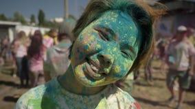 Το νέο ευτυχές ασιατικό κορίτσι χαμογελά και κλείνει το μάτι με τη ζωηρόχρωμη σκόνη στο φεστιβάλ holi στην ημέρα το καλοκαίρι, έν απόθεμα βίντεο