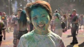 Το νέο ευτυχές ασιατικό κορίτσι χαμογελά με τη ζωηρόχρωμη σκόνη στο φεστιβάλ holi στην ημέρα το καλοκαίρι, προσέχοντας στη κάμερα απόθεμα βίντεο