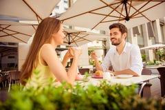 Το νέο ευτυχές ζεύγος κάθεται στο ελαφρύ πεζούλι υπαίθρια ο καφέδων ` s στοκ εικόνα με δικαίωμα ελεύθερης χρήσης