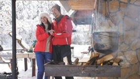 Το νέο ευτυχές ζεύγος μια χειμερινή ημέρα είναι έτοιμο στο προαύλιο ενός ξύλινου δασικού σπιτιού ανοίγει πυρ απόθεμα βίντεο