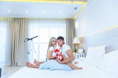Το νέο ευτυχές ζεύγος που βρίσκεται στο κρεβάτι, ισπανικός άνδρας δίνει στην έκπληξη γυναικών τον παρόντα φάκελο με την κορδέλλα, Στοκ Εικόνες