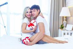 Το νέο ευτυχές ζεύγος που βρίσκεται στο κρεβάτι, ισπανικός άνδρας δίνει στην έκπληξη γυναικών τον παρόντα φάκελο με την κορδέλλα, Στοκ Φωτογραφία