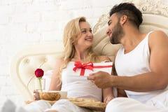 Το νέο ευτυχές ζεύγος που βρίσκεται στο κρεβάτι, ισπανικός άνδρας δίνει στην έκπληξη γυναικών τον παρόντα φάκελο με την κορδέλλα, στοκ εικόνα