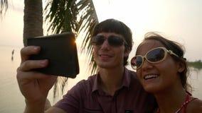 Το νέο ευτυχές ζεύγος στα γυαλιά ηλίου που συλλαμβάνει τις ρομαντικές διακοπές παίρνει ένα πορτρέτο selfie σε μια τροπική παραλία απόθεμα βίντεο
