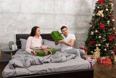 Το νέο ευτυχές ζεύγος στις πυτζάμες χαίρεται για το τους παρουσιάζει ενώ Si Στοκ Εικόνες