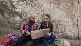 Το νέο ευτυχές ζεύγος των τουριστών μελετά έναν χάρτη, καθμένος σε μια πέτρα κοντά σε έναν μεγάλο βράχο, έναν άνδρα και τα backpa απόθεμα βίντεο