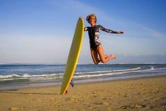 Το νέο ευτυχές και ελκυστικό άλμα κοριτσιών surfer υψηλό στον πίνακα κυματωγών εκμετάλλευσης αέρα πρίν κάνει σερφ στην όμορφη τρο στοκ φωτογραφία με δικαίωμα ελεύθερης χρήσης