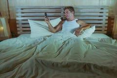 Το νέο ευτυχές και ελκυστικό άτομο μόνο στο κρεβάτι που χρησιμοποιεί τα κοινωνικά μέσα app στο κινητό τηλέφωνο χαλάρωσε και εύθυμ Στοκ φωτογραφία με δικαίωμα ελεύθερης χρήσης