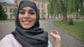 Το νέο ευτυχές μουσουλμανικό κορίτσι στο hijab κάνει τηλεοπτικός, ρητό hey, ο κυματισμός παραδίδει τον μπλε καιρό, έννοια επικοιν απόθεμα βίντεο