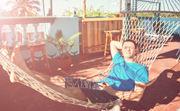 Το νέο εύθυμο άτομο βρίσκεται υπόλοιπο της Κούβας ηλιοφάνειας patio αιωρών Στοκ Εικόνα