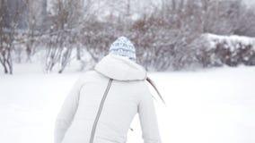 Το νέο εύθυμο κορίτσι περπατά το χειμώνα στο πάρκο, που παίζει στο χιόνι, κρύο φιλμ μικρού μήκους