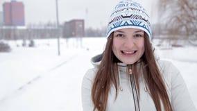 Το νέο εύθυμο κορίτσι περπατά το χειμώνα στο πάρκο, που παίζει στο χιόνι, κρύο απόθεμα βίντεο