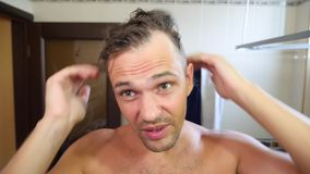Το νέο ελκυστικό άτομο επιθεωρεί υποχωρώντας hairline στο λουτρό _ 4k, σε αργή κίνηση απόθεμα βίντεο