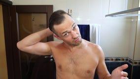Το νέο ελκυστικό άτομο επιθεωρεί υποχωρώντας hairline στο λουτρό _ 4k, σε αργή κίνηση φιλμ μικρού μήκους
