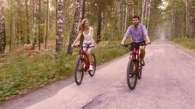 Το νέο ελκυστικό ζεύγος αρχίζει να κινείται στα ποδήλατα στο θερινό πάρκο απόθεμα βίντεο