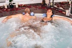 Το νέο ελκυστικό ζεύγος χαλαρώνει στην καυτή σκάφη στοκ εικόνα