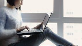 Το νέο, ελκυστικό κορίτσι κάθεται από το παράθυρο με ένα lap-top Όμορφη επιχειρησιακή γυναίκα brunette που εργάζεται στον υπολογι απόθεμα βίντεο