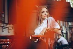 Το νέο ελκυστικό κορίτσι στο άσπρο πουκάμισο με μια συνεδρίαση saxophone caffe πλησίον ψωνίζει - υπαίθριος σε sity Προκλητική νέα Στοκ φωτογραφίες με δικαίωμα ελεύθερης χρήσης