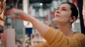 Το νέο ελκυστικό κορίτσι στο κατάστημα επιλέγει τα φω'τα αστεριών λαμπτήρων, ντεκόρ Χριστουγέννων απόθεμα βίντεο