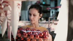 Το νέο ελκυστικό κορίτσι brunette στο κατάστημα επιλέγει τους λαμπτήρες, ντεκόρ Χριστουγέννων απόθεμα βίντεο