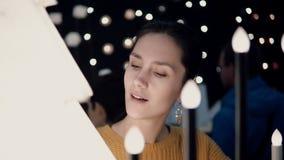 Το νέο ελκυστικό κορίτσι brunette στο κατάστημα επιλέγει τους λαμπτήρες, ντεκόρ Χριστουγέννων φιλμ μικρού μήκους