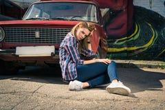 Το νέο ελκυστικό πρότυπο κάθεται κοντά στο αναδρομικό αυτοκίνητο Στοκ Φωτογραφίες