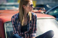 Το νέο ελκυστικό πρότυπο κάθεται κοντά στο αναδρομικό αυτοκίνητο Στοκ Εικόνα