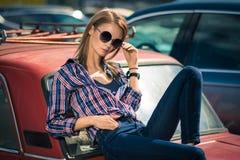 Το νέο ελκυστικό πρότυπο κάθεται κοντά στο αναδρομικό αυτοκίνητο Στοκ Εικόνες