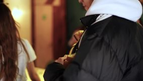 Το νέο ζευγάρι έρχεται στον καφέ και το ευγενικό ενισχυμένο τύπος χαριτωμένο κορίτσι να βγάλει το κίτρινο σακάκι πρίν πηγαίνει στ απόθεμα βίντεο