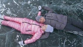 Το νέο ζεύγος έχει τη διασκέδαση κατά τη διάρκεια του χειμερινού περιπάτου στο κλίμα του πάγου της παγωμένης λίμνης Οι εραστές βρ απόθεμα βίντεο