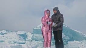 Το νέο ζεύγος έχει τη διασκέδαση κατά τη διάρκεια του χειμερινού περιπάτου στο κλίμα του πάγου της παγωμένης λίμνης Οι εραστές έχ απόθεμα βίντεο