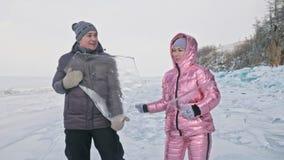 Το νέο ζεύγος έχει τη διασκέδαση κατά τη διάρκεια του χειμερινού περιπάτου στο κλίμα του πάγου της παγωμένης λίμνης ιστορία αγάπη φιλμ μικρού μήκους
