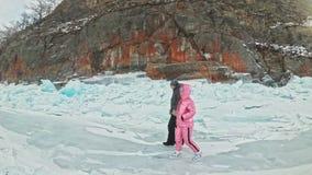 Το νέο ζεύγος έχει τη διασκέδαση κατά τη διάρκεια του χειμερινού περιπάτου στο κλίμα του πάγου της παγωμένης λίμνης Οι εραστές πε απόθεμα βίντεο