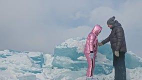 Το νέο ζεύγος έχει τη διασκέδαση κατά τη διάρκεια του χειμερινού περιπάτου στο κλίμα του πάγου της παγωμένης λίμνης Οι εραστές έχ φιλμ μικρού μήκους