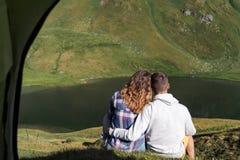 Το νέο ζεύγος αγκαλιάζει το ένα το άλλο μπροστά από μια σκηνή στα βουνά της Ελβετίας στοκ εικόνες