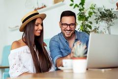 Το νέο ζεύγος εργάζεται στον καφέ στο lap-top και το χαμόγελο - Εικόνα στοκ φωτογραφίες