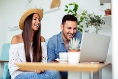 Το νέο ζεύγος εργάζεται στον καφέ στο lap-top και το χαμόγελο - Εικόνα στοκ εικόνα
