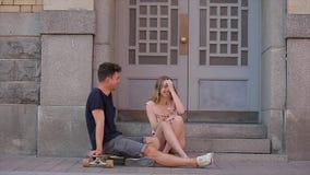 Το νέο ζεύγος ερωτευμένο κάθεται στα βήματα κατώτατων ορίων στην προοπτική και τη συζήτηση Nevsky στην slo-Mo φιλμ μικρού μήκους