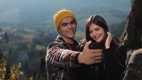 Το νέο ζεύγος ερωτευμένο κάθεται υψηλό σε έναν βράχο στο βουνό και selfie στο τηλέφωνο κίνηση αργή φιλμ μικρού μήκους