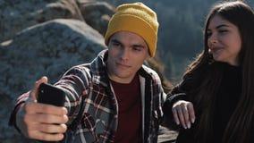 Το νέο ζεύγος ερωτευμένο κάθεται υψηλό σε έναν βράχο στο βουνό και selfie στο τηλέφωνο κίνηση αργή απόθεμα βίντεο